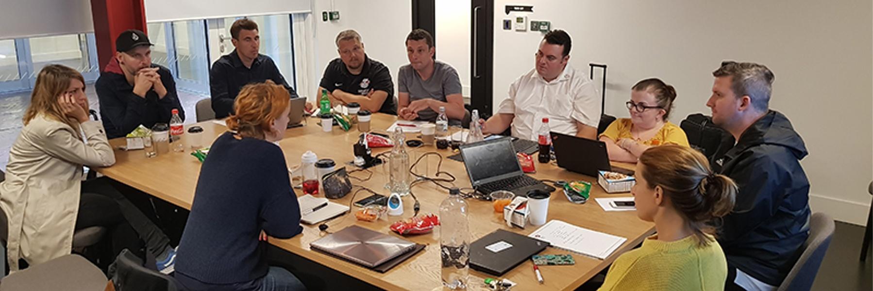 Teilnehmer*innen des Treffens sitzen rund um einen Tisch in einem Besprechungsraum und unterhalten sich.
