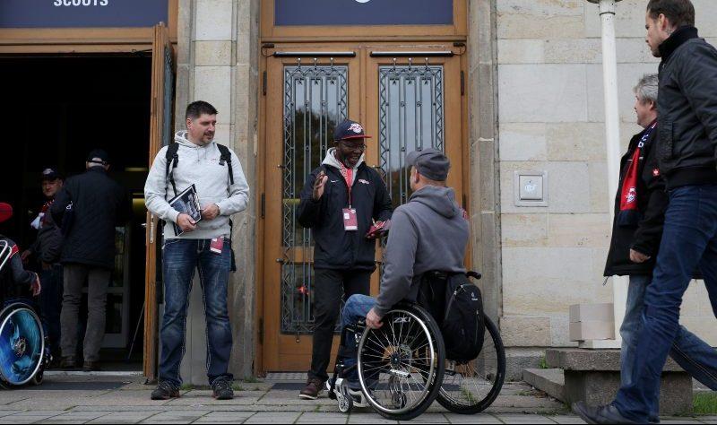 RB Leipzig Rollstuhlfahrer im Gespräch mit dunkelhäutigem Mitarbeiter der Behindertenbetreuung vor dem Eingang eines Fanraumes.