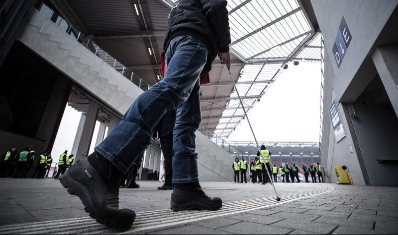 Ein blinder Fan mit Blindenstock orientiert sich an den Bodenmarkierungen im Stadion von Mainz 05. Er geht Richtung Tribüne.