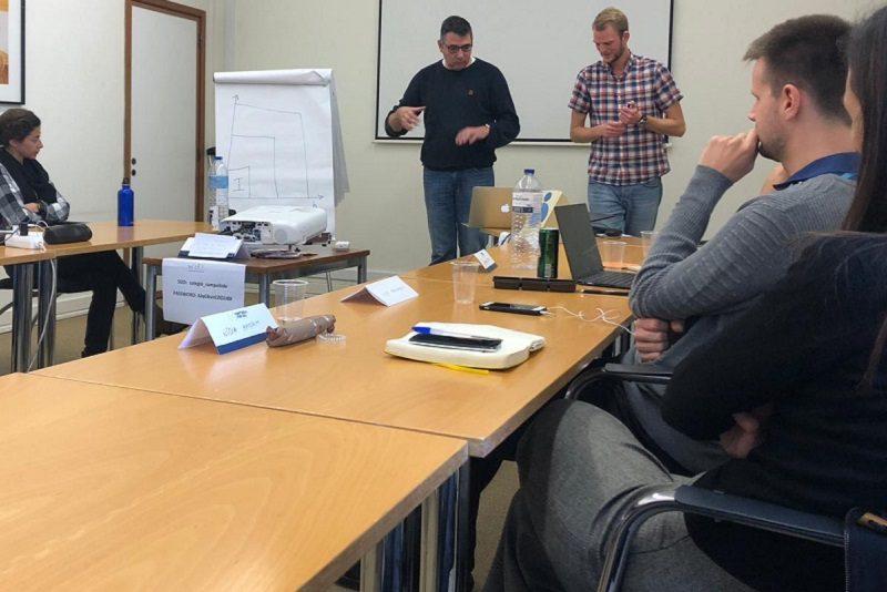 Teilnehmer stellen Arbeitsergebnisse vor einer Gruppe vor.