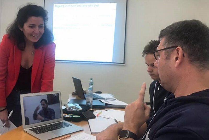 zwei Personen arbeiten an einem Laptop, eine Schulungsleiterin steht daneben. Alle sind im Gespräch