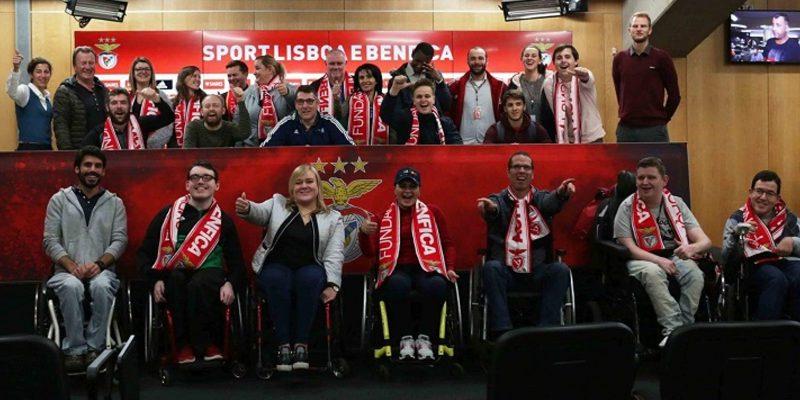 Football For all Teilnehmer*innen, teilweise im Rollstuhl, lachen freudig in die Kamera. Manche haben einen Fanschal von Lissabon um.