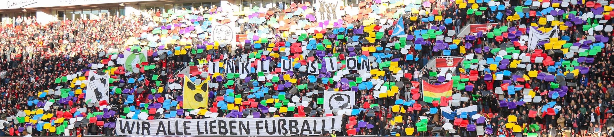 Choreographie Fans Leverkusen zum Thema Inklusion - Fans halten bunte Karten und Banner mit verschiedenen Bedeutungen von Inklusion hoch. Vorne ein Banner mit der Aufschrift: Wir alle lieben Fußball