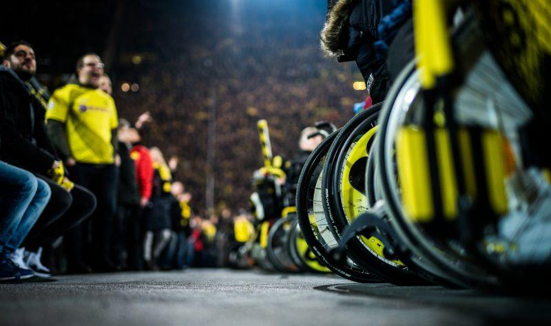 Borussia Dortmund Tribüne. Schwarz-gelbe Räder von Rollstühlen, dahinter Fans mit und ohne Trikots.