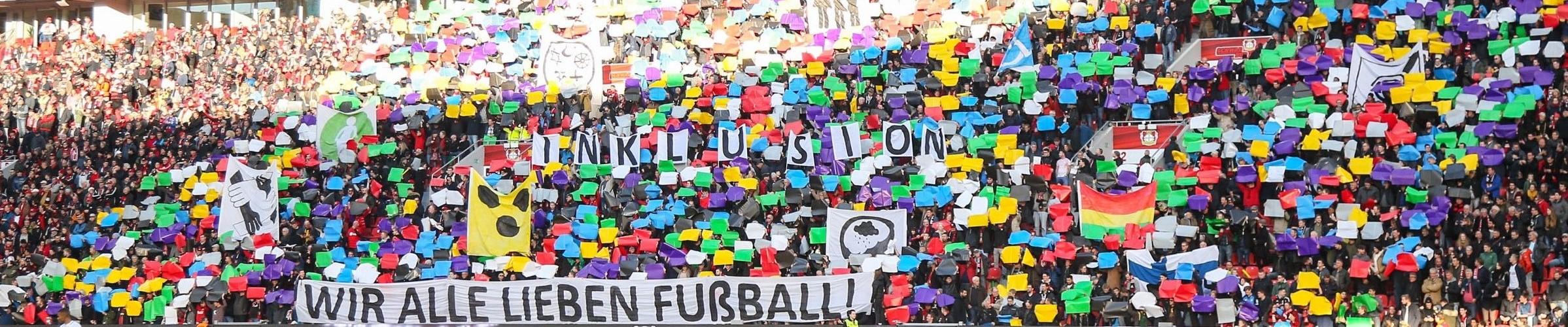 Choreographie Inklusion von Bayer 04 Leverkusen: Viele bunte Fahnen, selbst gestaltete Symbole zu Inklusion und Schriftzug: Inklusion wir alle lieben Fußball werden hochgehalten.