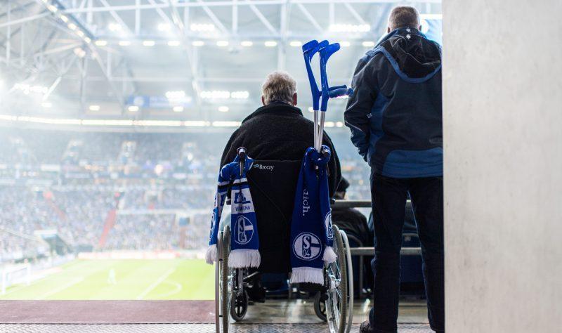 Rollstuhlfahrer mit Schalkeschals am den Griffen des Rollstuhls auf der Tribüne mit Blick auf das Spielfeld. Daneben ein stehender Fan.