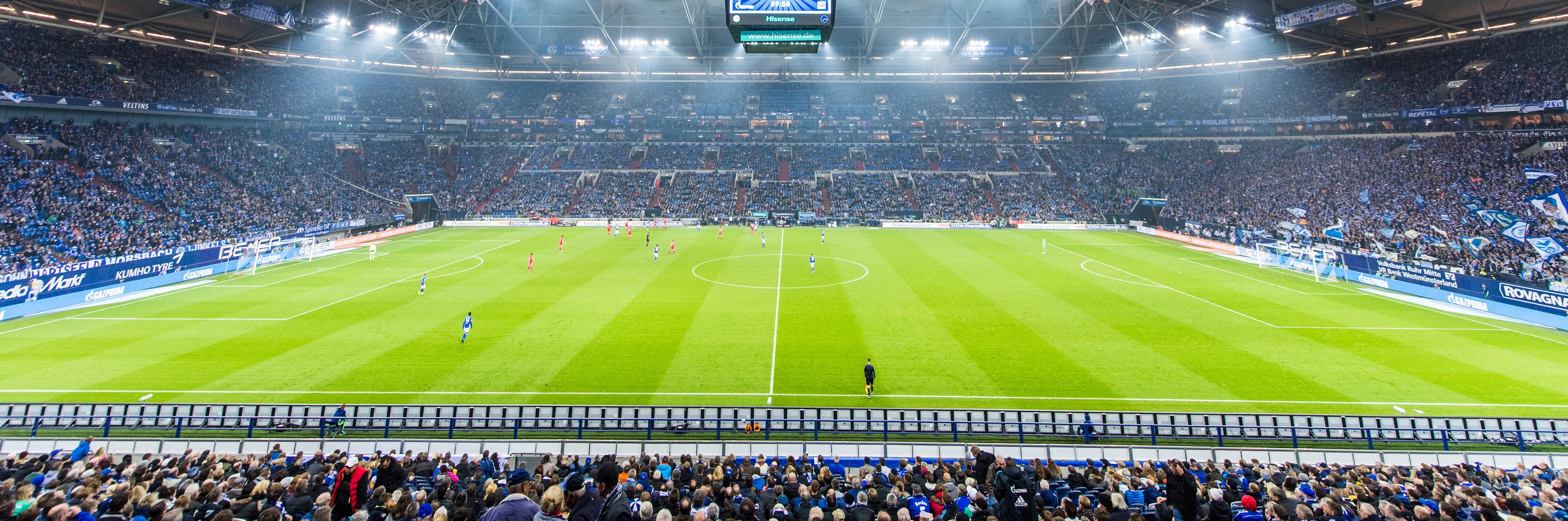 Blick auf das Spielfeld des Stadions von Schalke 04. Man sieht auch einen Teil der Zuschauer auf den Tribünen. Das Flutlicht ist an.