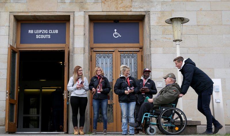farbiger Mitarbeiter und weibliche Mitarbeiterinnen mit Rollstuhlfahrer bei RB Leipzig