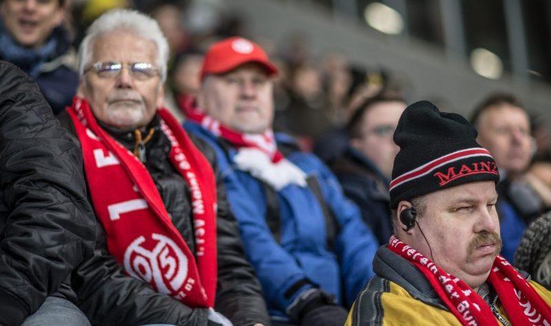 Ältere Fans von Mainz 5 auf der Tribüne mit Fanschals. Einer mit Fan-Cappy. Davor sitzt ein sehbehinderter Fan mit Kopfhörern.