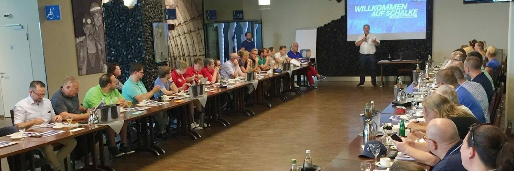 Teilnehmer*innen sitzen sich an Tischen gegenüber. Vorne steht eine Leinwand. Davor steht ein Person und erzählt etwas.