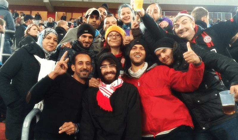Mitglieder des Fanclubs Yalla Yalla F95 von Fortuna Düsseldorf posieren auf der Tribüne. Zu dem Fanclub gehören viele Migranten und Migrantinnen.