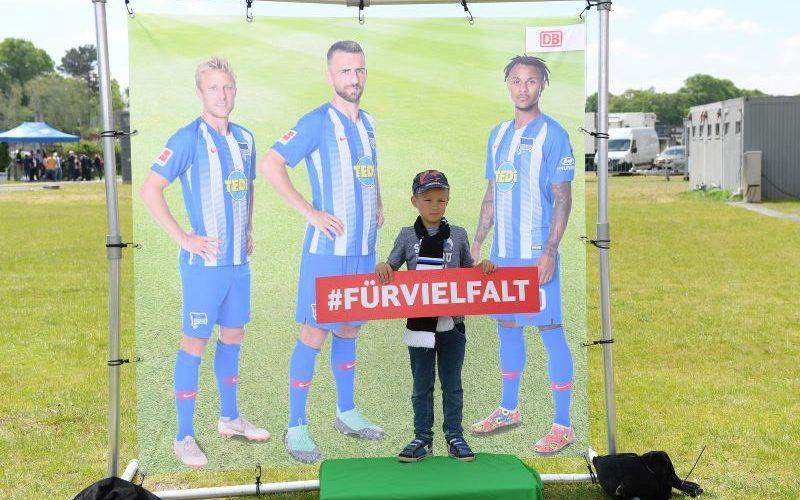 """Fotoleinwand mit drei Spielern drauf, davor lässt sich ein Junge mit Schild, auf dem steht """"für Vielfalt"""" ,fotografieren"""