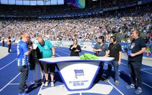 Stadionmoderatoren mit Gebärdensprachdolmetscherin interviewen Gäste im Innenraum