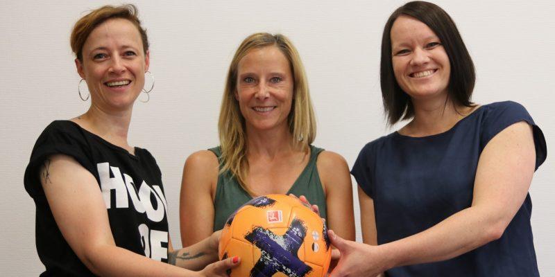 Daniela Wurbs, Projektleitung KickIn!; Stephanie Blume, Leitung Alles klar für alle; Nadja Peek, Mitarbeiterin KickIn! Sie halten gemeinsam einen Fußball und lächeln in die Kamera.