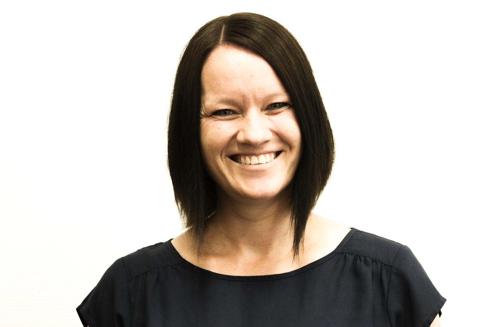 Nadja Peek - braune kurze Haare, lächelt in die Kamera, steht vor weißem Hintergrund