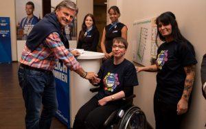 mehrere Personen an einem Infostand: Eine Rollstuhlfahrerin mit Betreuerin im Inklusions-T-Shirt und weitere Personen