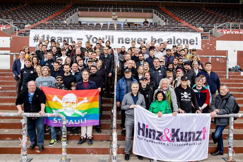 zeigt insgesamt 100 Mitarbeiter*innen und Präsidium des FC St. Pauli und des Strassenmagazins Hinz & Kunzt