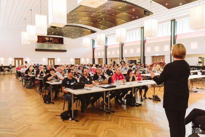 Die Gebärdensprachdolmetscherin übersetzt während der Tagung. Sie steht vorne vor den TeilnehmerInnen.