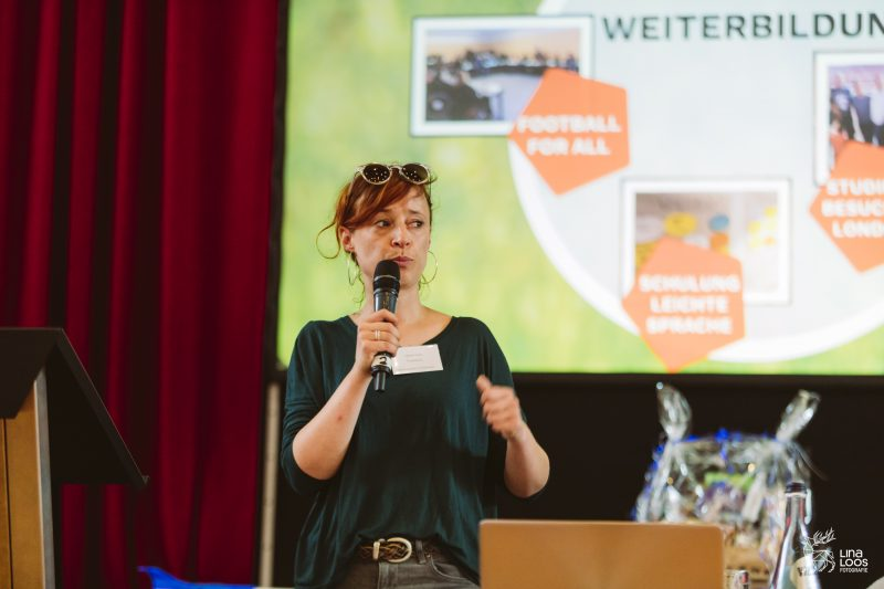 Daniela Wurbs trägt den Tätigkeitsbericht von KickIn! vor. Hinter ihr auf der Leinwand eine Präsentation zum Bericht.
