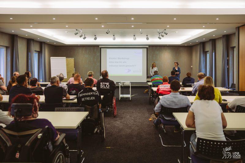 Workshop Leichte Sprache, TeilnehmerInnen im Seminarraum von hinten fotografiert, vorne Stefanie Blume - Seminarleiterin und Daniela Wurbs, daneben wird auf einer Leinwand Informationen angezeigt.