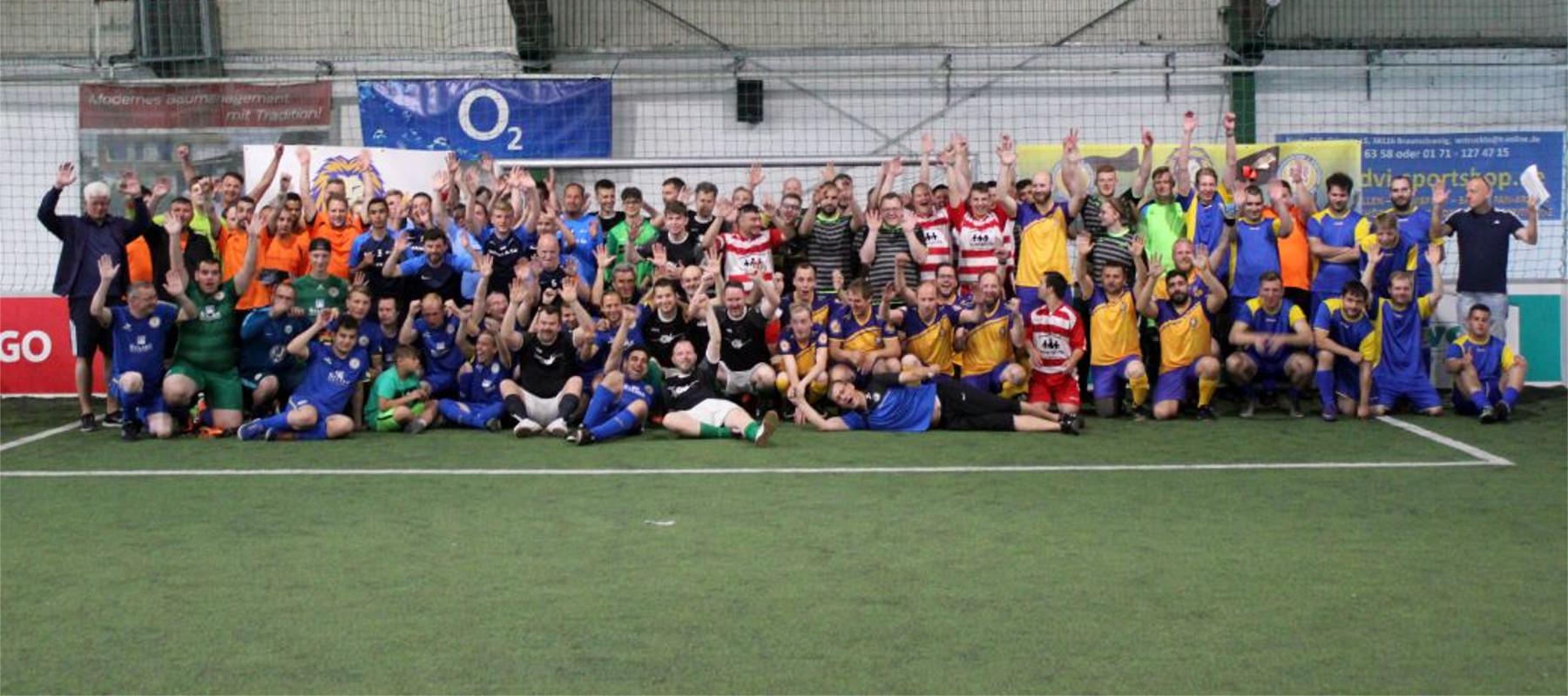 Die verschiedenen Mannschaften posieren gemeinsam auf dem Spielfeld im Strafraum.