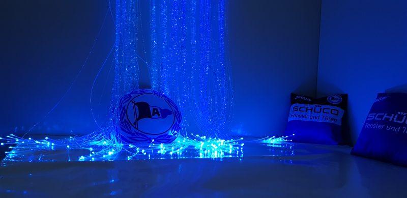 blaue Beleuchtung im Snoezelraum, Blick auf Fasernebel, welcher an den Enden heller leuchtet. Zusätzlich sind Arminia Bielefeld Kissen zu sehen.