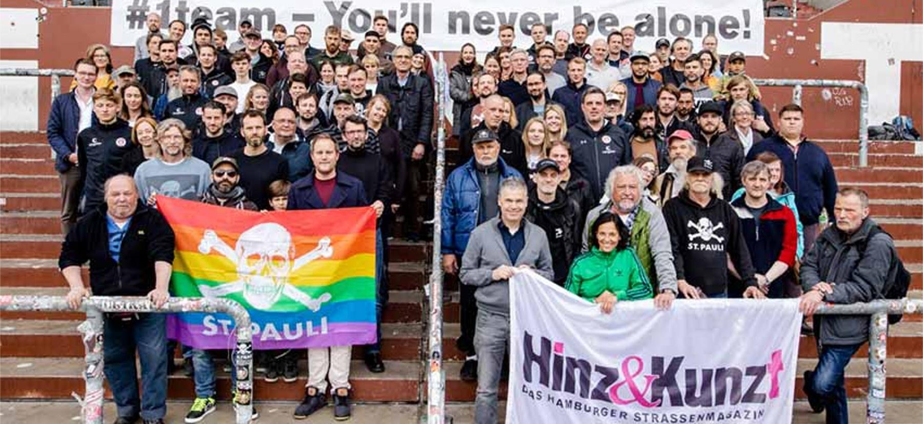 insgesamt 100 Mitarbeiter*innen und Präsidium des FC St. Pauli und des Strassenmagazins Hinz & Kunzt. Sie stehen auf der Tribüne des FC St. Pauli. Vorne werden je eine Fahne vom FC St. Pauli und des Straßenmagazins hochgehalten.