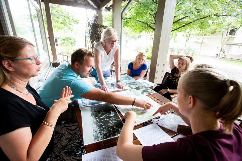 Teilnehmer*innen besprechen in einer kleinen Gruppe alte Fotos.