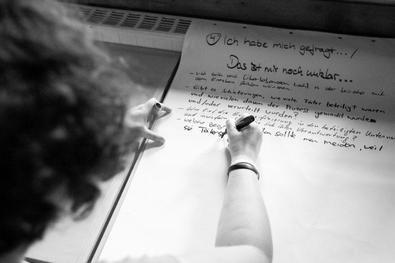 eine Teilnehmerin schreibt auf einem großen Blatt, was ihr noch unklar ist - schwarz-weiß Fotografie