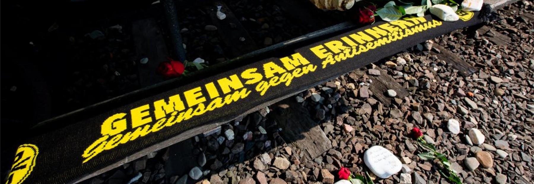 Schal in schwarz-gelb mit der Aufschrift Gemeinsam erinnern
