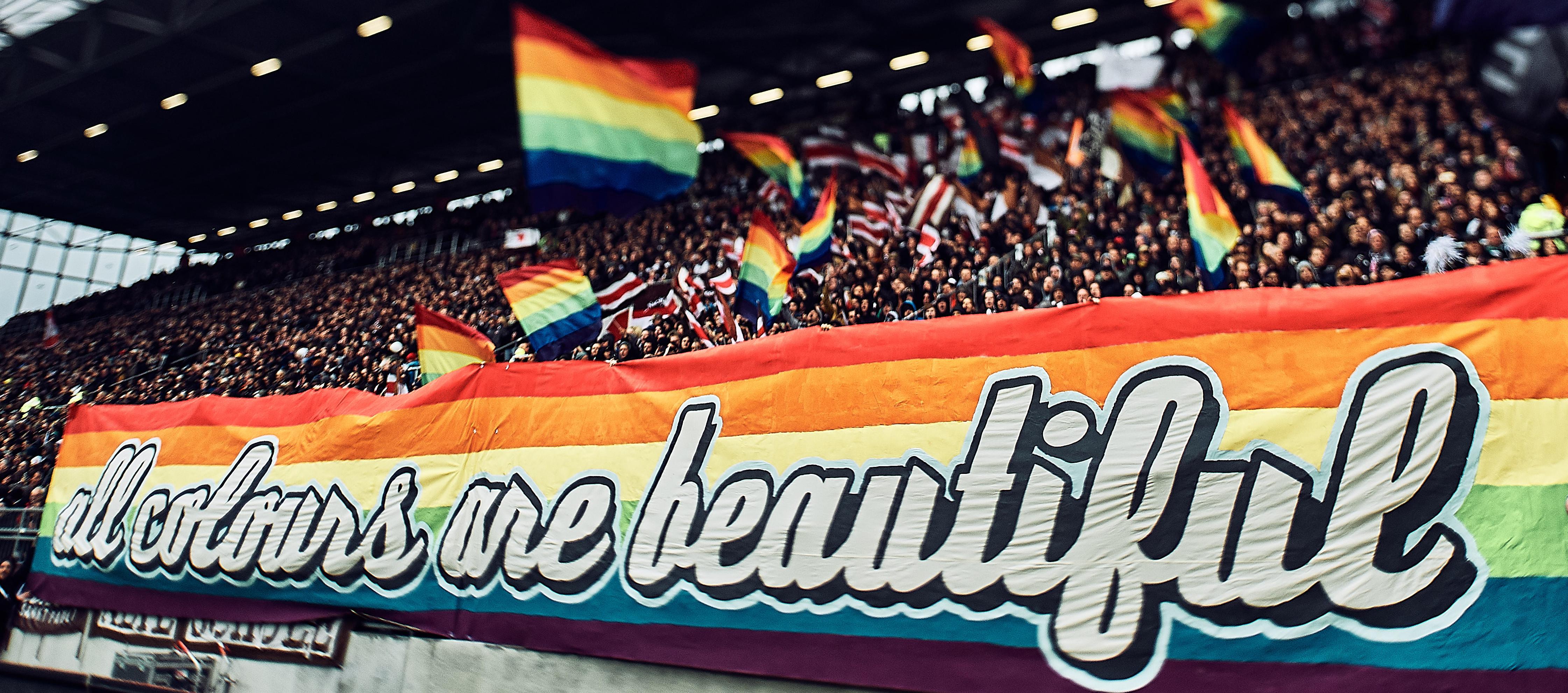 """Choreographie St. Pauli. Unten Banner in Regenbogenfarben mit Aufdruck """"all colours are beautiful"""". Darüber schwingen Fans bunte Fahnen."""