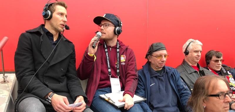 zwei Blindenreporter bei der Reportage. Daneben sitzen zwei Fans mit Kopfhörern.