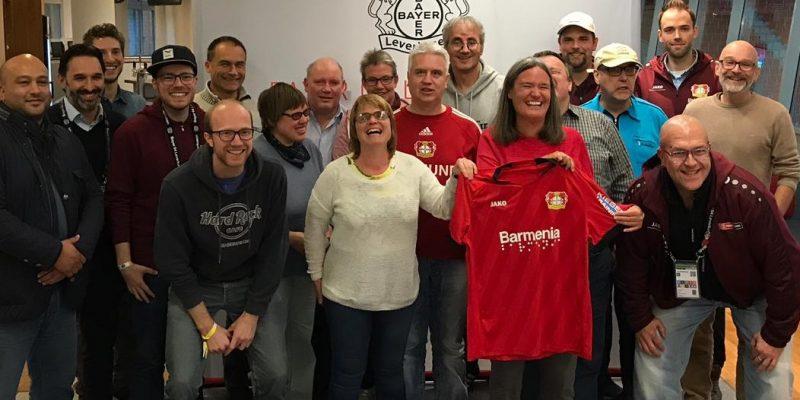 Team der Behindertenfanbetreuung und hörbehinderte Fans stehen vor einem Banner mit dem Logo von Bayer 04 Leverkusen, lachen in die Kamera. Eine Frau hält das Bayer Leverkusen Trikot mit der Brailleschrift auf dem Ärmel hoch.