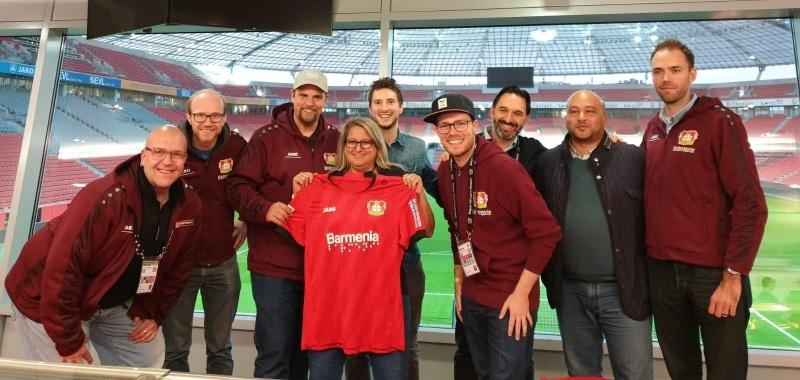 Team der Behindertenfanbetreuung und Blindenreporter in einer Loge im Stadion. In der Mitte steht Alexandra Lüddecke von der BBAG und hält ein Bayer Leverkusen Trikot mit der Brailleschrift auf dem Ärmel, hoch.