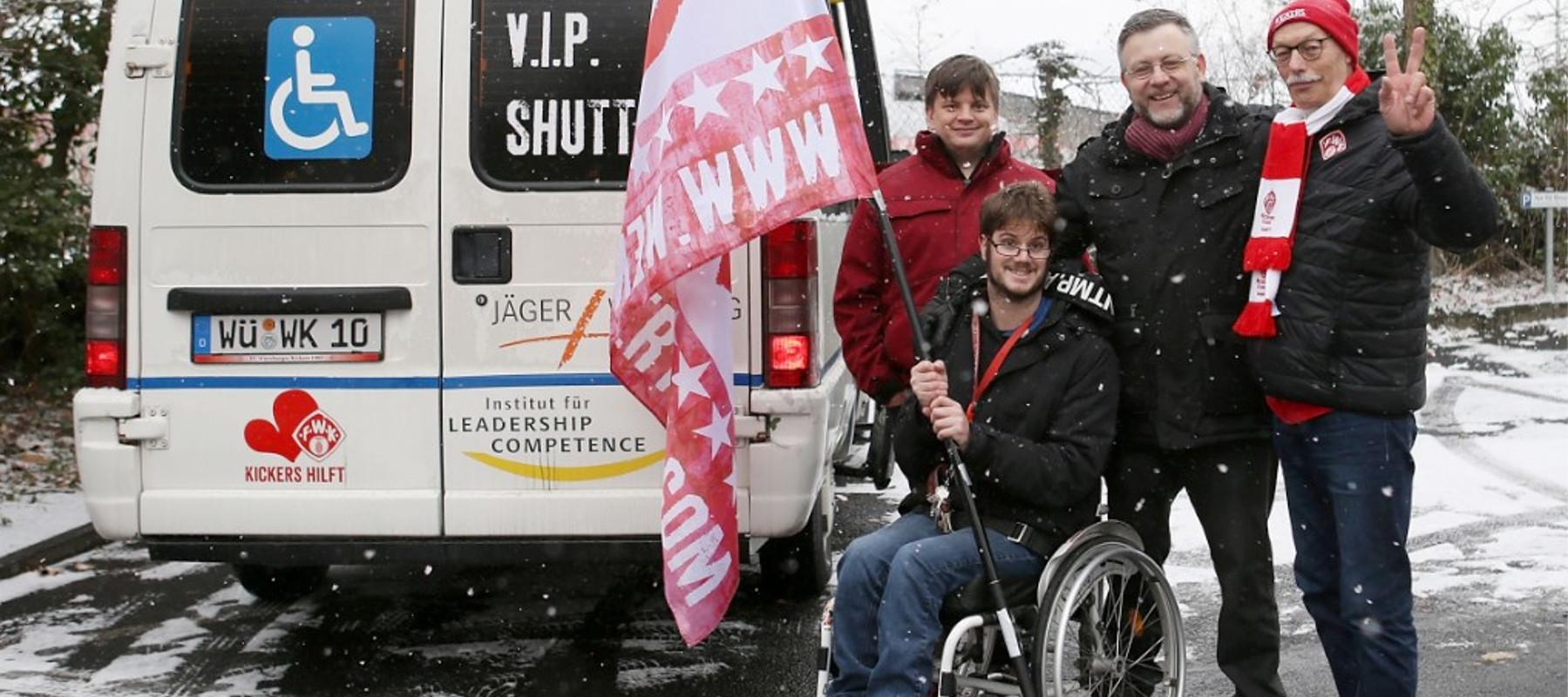 """Vier Personen stehen neben einem weißen Transporter. Einer davon Rollstuhlnutzer. Erhält eine große Schwenkfahne. Auf dem Fahrzeug steht der Schriftzug """"VIP Shuttle""""."""