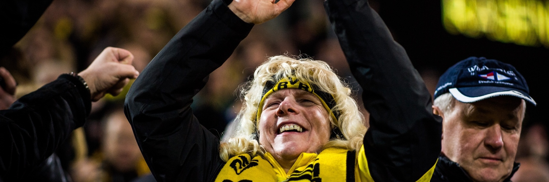 blinde Anhängerin von Borussia Dortmund freut sich, klatscht mit den Händern über dem Kopf. Sie ist mit einem Dortmund Trikot und Schal bekleidet.