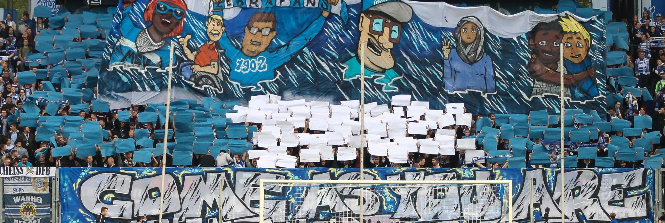 Choreographie zu Inklusion vom MSV Duisburg. Oben: Banner unterschiedlicher Menschen: dunkelhäutige, blind Frau mit dunkler Brille, Rollstuhlfahrer, Frau mit Kopftuch, gleichgeschlechtliches Paar. Davor blau weiße Schilder. Unten: Banner mit der Aufschrift: Come as you are