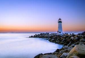 rechts im Bild ein Leuchtturm an einer Steinküste bei Sonnenuntergang, links das Wasser