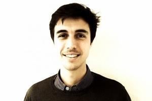 Carlo Kosok: dunkelbraune, kurze Haare lächelt in die Kamera. Er steht vor einem weißen Hintergrund.