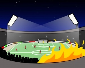 Bild eines Stadions. Rechts auf der Tribüne brennt es, links davon drängen sich die Zuschauer*innen zusammen.