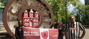 Drei Personen halten ein Banner der weiß braunen Kaffeetrinker*innen hoch. Sie stehen vor eine großen St. Pauli Logo