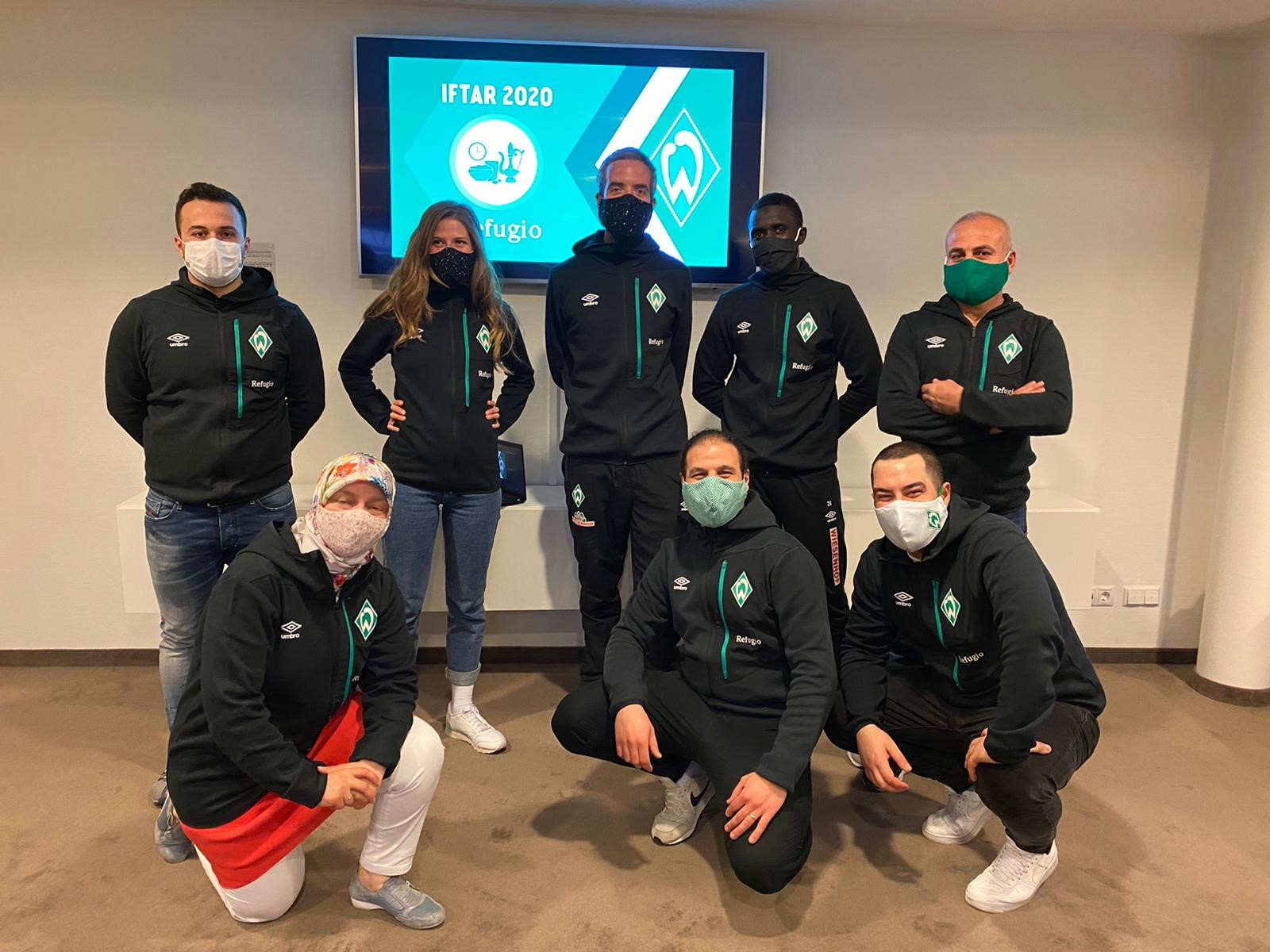 Trainer*innen des SV Werder Bremen stehen mit Mund-Nasen-Schutz nebeneinander.