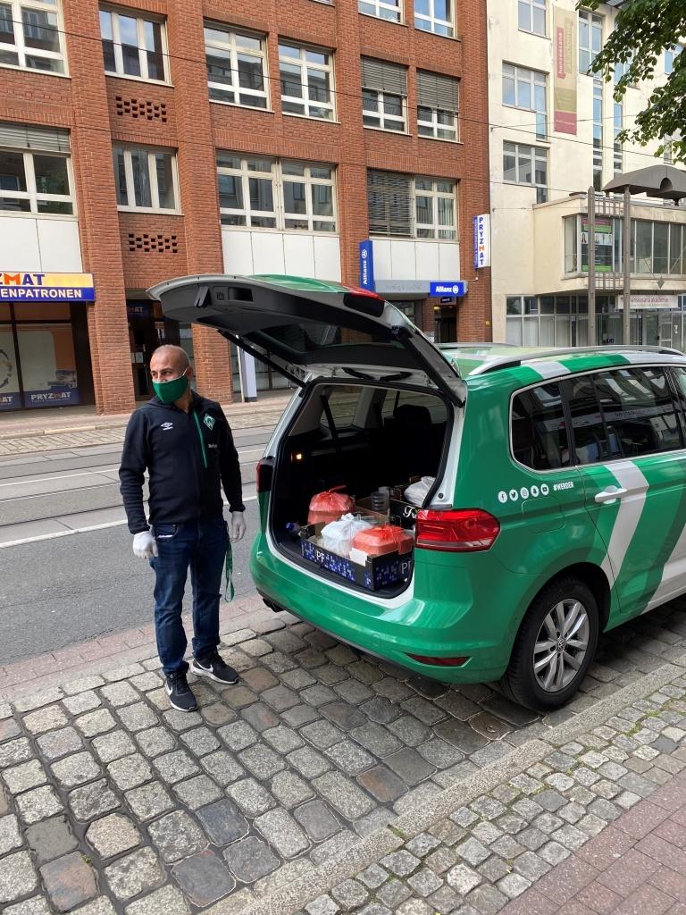 Ein Mann steht vor einem grünen Auto, welches mit Mahlzeiten beladen ist.