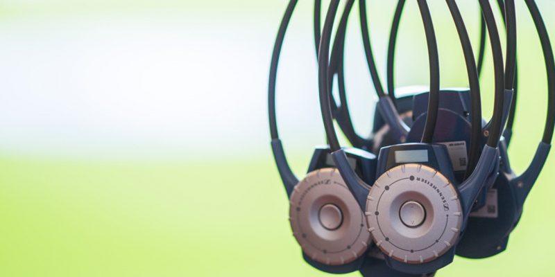 Ein Bündel spezieller Funkempfänger vor einem grünen Rasen. Mit diesen Geräten sind die audiodeskriptiven Reportagen in Bundesliga-Stadien zu hören.