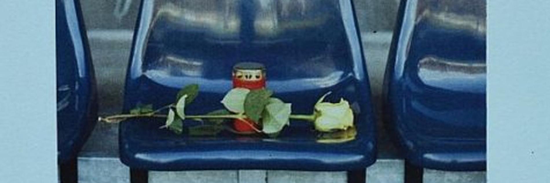 Eine weiße Rose und eine rote Grabkerze auf einem leeren Stadionsitz.