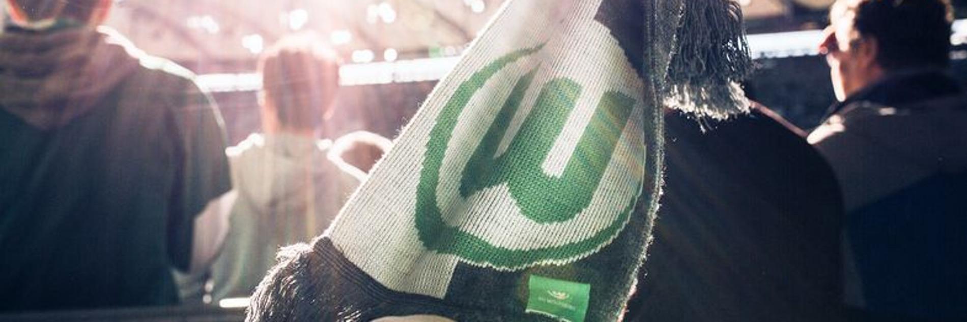Schal mit VfL Wolfsburg-Logo wird im Stehplatz-Bereich der Volkswagen Arena gegen die Sonne gehalten.