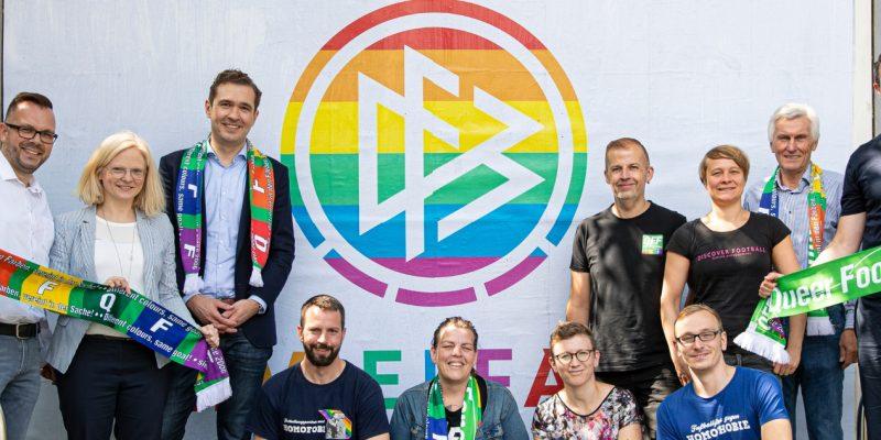 DFB-Logo in Regenbogenfarben auf einer Plakatwand. Davor versammelten sich Fans, die sich gegen Homophobie im Fußball engagieren.