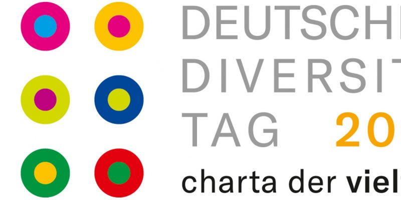 """Das Logo des Deutschen Diversity-Tages: 9 bunte Punkte mit jeweils einem andersfarbigem Kreis drum. Daneben ein """"Deutscher Diversity-Tag 2021 - charta der vielfalt""""-Schriftzug."""