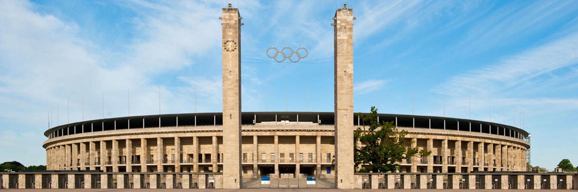 Der Haupteingang (Osttor) vom Olympiastadion Berlin vor blauem Himmel von außen fotografiert. Zwischen zwei Türmen sind die fünf olympischen Ringe sowie die Stadionränge von hinten zu sehen.
