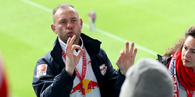 Fans im Gehörlosenblock von RB Leipzig mit Blick auf einen Gebärdensprachdolmetscher bei der Arbeit.
